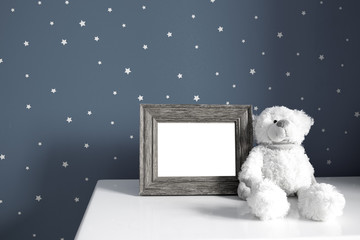 Empty photo wooden frame and white teddy bear in the dark nursery