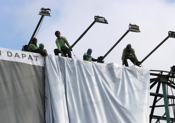 Workers roll an advertising billboard along main road EDSA in preparation for the coming of Super Typhoon Mangkhut in Quezon City