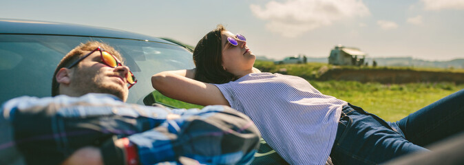 Young couple resting lying on the windshield and the hood of the car