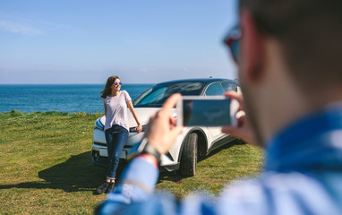 Young man taking a picture of a girl leaning on a car near the coast