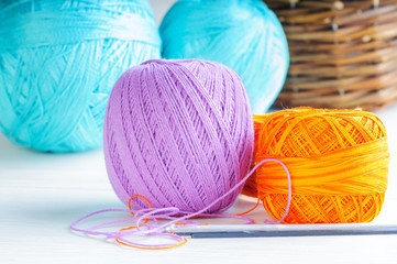 Yarn balls and crochets on the wooden background