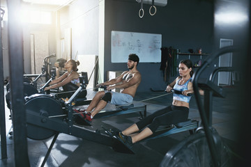 Crossfit. People Exercising On Rowing Machine In Training Gym