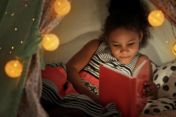 Little African-American girl reading bedtime story in hovel Wall mural