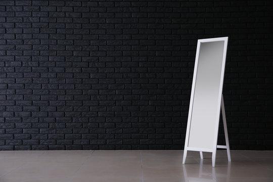 Large mirror near dark brick wall