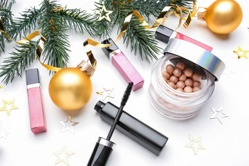 Set of cosmetics with Christmas decorations on white background