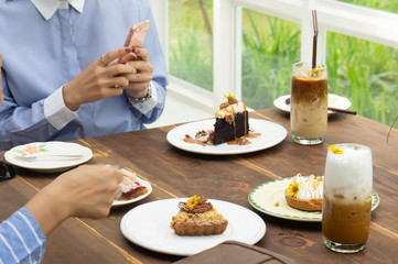 women talking and take a photo dessert and food in cafe restaurant, enjoy eating