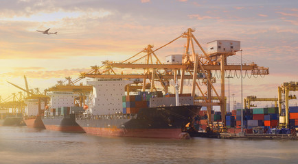 The port atmosphere while beautiful sunset with all cargo ships are berthing and do cargo operation busy status with airplane on the sky at background as for shipping and ligistics industry concept.