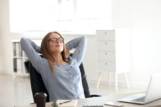 Young businesswoman relaxing at workplace in office