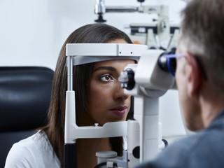Optometrist examining young woman's eye