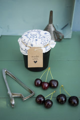 Glass of homemade cherry jam, cherries and pit remover