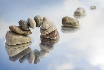 arch of balanced pebbles and stepping stones in the water with reflection, light blue sky with clouds, copy space
