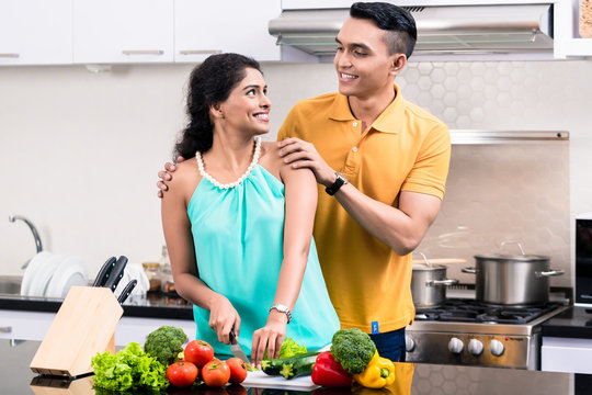 Young smiling couple looking at each other standing in kitchen