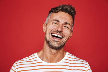 Handsome guy with stubble in striped t-shirt laughing on camera, isolated over red background