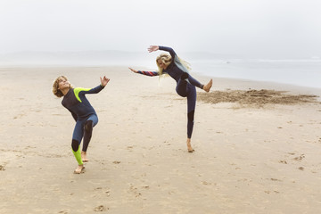 Spain, Aviles, two young surfers warming up before surfing