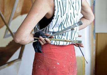 Female painter in her atelier, holding paintbrushes in her hand