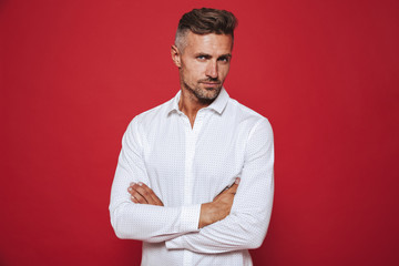Masculine brunette man 30s with stubble in white shirt looking on camera, isolated over red background