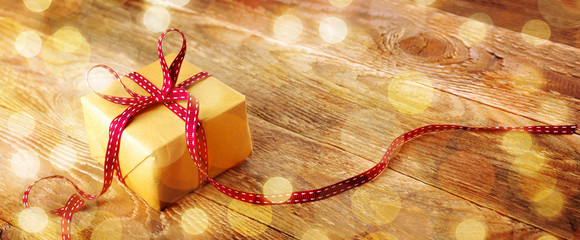 Gift box with magic lights on old rustic wood  -- festive background
