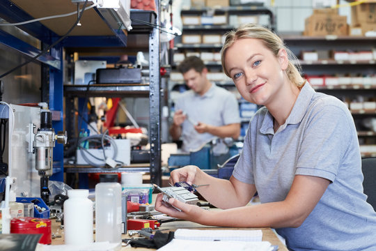 Portrait Of Female Engineer In Factory Measuring Component At Work Bench Using Micrometer