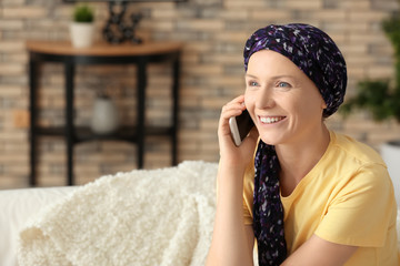 Woman after chemotherapy talking on mobile phone at home