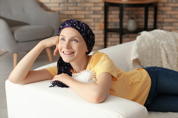 Woman after chemotherapy lying on sofa at home