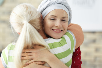 Woman after chemotherapy hugging her mother at home