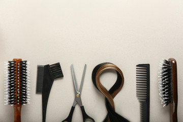 Professional hairdresser's set with strands of hair on light background