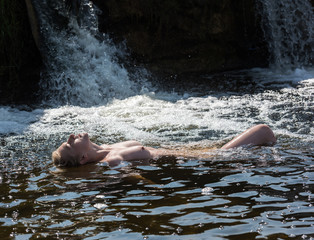 Poster Akt Beautiful young nude woman enjoying summertime in waterfall.