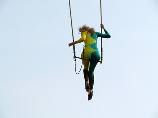 Girl aerial acrobat sitting on trapeze on sky background during a street circus performance. Woman gymnast performs acrobatic tricks