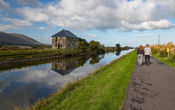 Couple walking on a river canal path beside an abandonned house near Blennerville in County Kerry, Ireland
