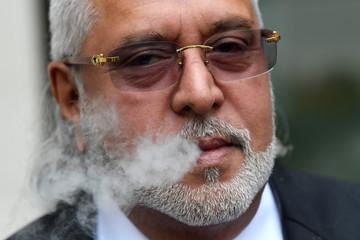 Vijay Mallya smokes outside Westminster Magistrates Court in London