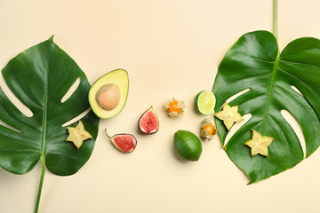 Wall Mural - Summer composition with fresh monstera leaves and fruits on light background