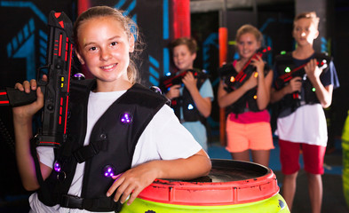 Girl with laser pistol in lasertag room