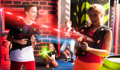 Girls and boys playing laser tag
