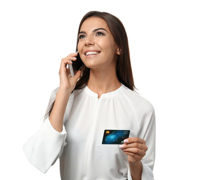 Young woman with credit card talking on mobile phone against white background. Online shopping