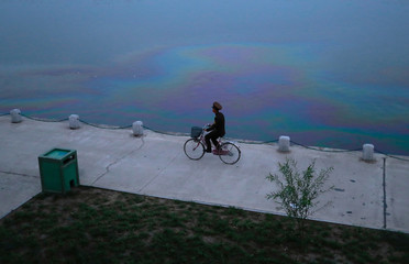 A soldier rides a bicycle along the Taedong river in Pyongyang