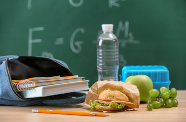 Bag with notebooks and appetizing food on table in classroom