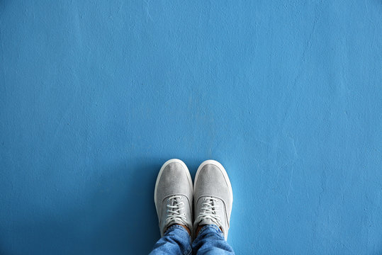 Legs of man in casual shoes on color background