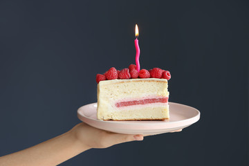 Woman holding piece of delicious birthday cake with burning candle on grey background