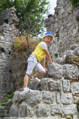 boy climbs the ruins of an ancient building