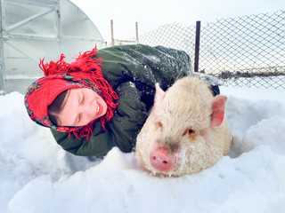 Cute peasant woman in traditional Russian red kerchief  holds piglet covered with ice and hoarfrost. Swine stuck in snow after blizzard and needed help. Christmas story. 2019 Year Yellow pig