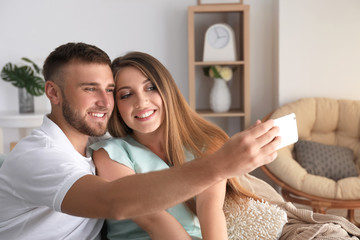 Happy loving couple taking selfie at home