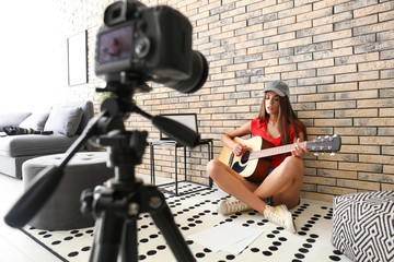 Young female musician recording video indoors