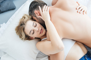 top view of shirtless man hugging and kissing attractive girlfriend on bed