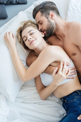 top view of handsome bearded man hugging and kissing smiling girlfriend in bedroom