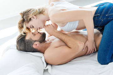 side view of passionate young couple able to kiss in bed
