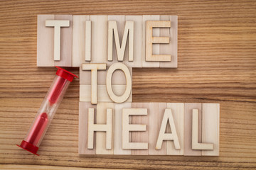 time to heal-  text in vintage letters on wooden blocks. Medicine concept