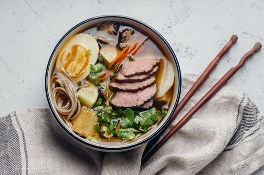 Miso ramen with roasted beef, shiitake mushrooms, fried tofu, leek and eggs on concrete background. Top view. Lunch in asian style