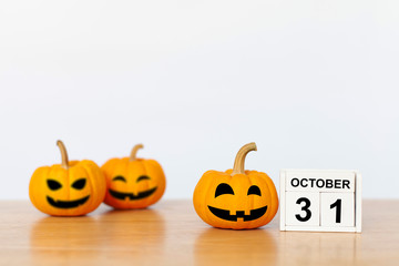 Wooden cubes with the numbers 31 october and pumpkin on wood table with white background. Halloween celebration concept. copy space