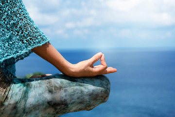 Woman sitting in yoga on mountain near the Andaman Sea. On holiday season of the summer Relaxing muscles meditating with nature. Bright sunshine The body is getting healthy vitamin. close up for hand