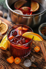 Glass of delicious mulled wine on wooden board